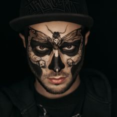 A guy with a butterfly and skulls painted on his face